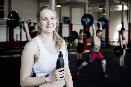 Fit Woman Holding Water Bottle In Gym