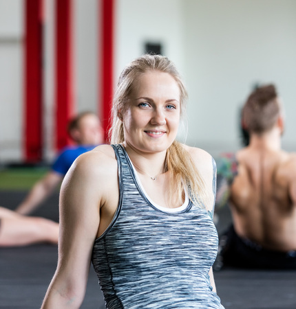 Woman Resting While Sitting On Floor In Gym