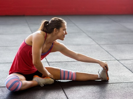 Woman Doing Stretching Exercise In Gym