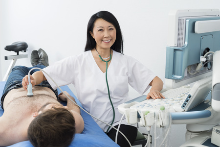Smiling Doctor Performing Ultrasound Test On Patient In Hospital