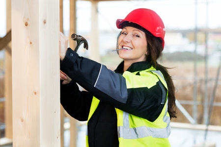 Portrait Of Happy Female Carpenter Hammering Wood Archivio Fotografico