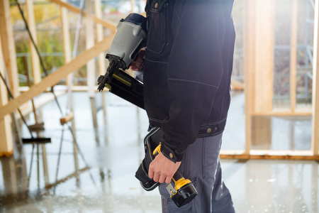 Midsection Of Carpenter With Drill Machines At Site