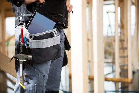 Young Carpenter With Tablet Computer And Tools In Bag At Site Foto de archivo