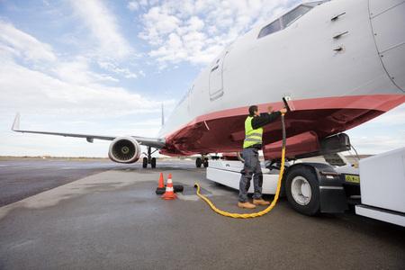 Full Length Of Crew Member Charging Airplane
