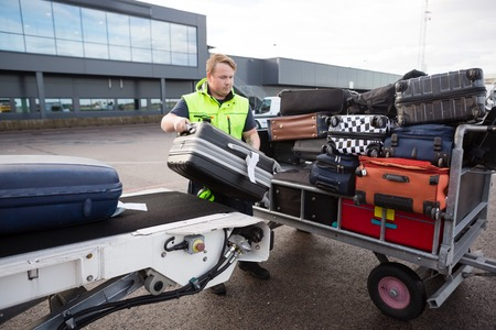 Worker Stacking Luggage On Trailer From Conveyor On Runway Imagens - 90465405
