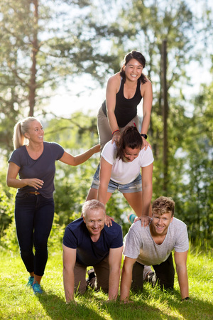 Smiling Coworkers Making Human Pyramid On Grassy Field
