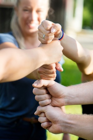 Cropped Image Of Friends Stacking Fists