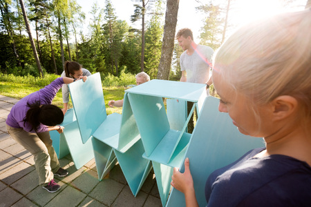 Woman Looking At Friends Making Pyramid Of Wooden Planks