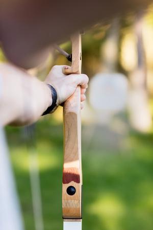 Giovane uomo d'affari che mira freccia al bordo dell'obiettivo in foresta