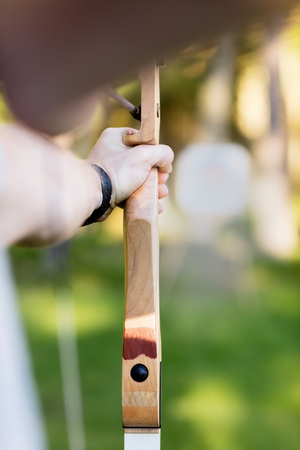 Young Businessman Aiming Arrow At Target Board In Forest