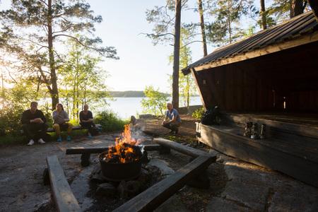 Firepit bruciante di legno con gli amici che si rilassano nella foresta