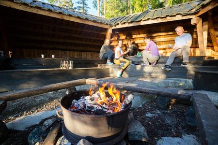Firepit bruciante con gli amici che preparano alimento in tettoia Archivio Fotografico