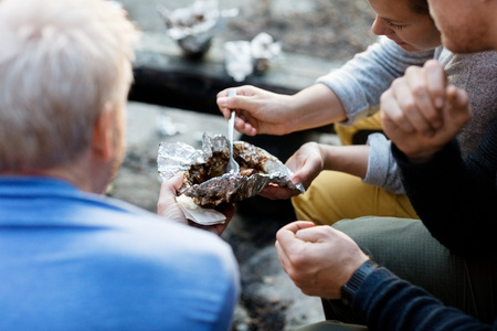 Friends Having Food In Foil At Forest