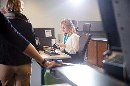 Staff Examining Boarding Pass Of Passenger At Airport