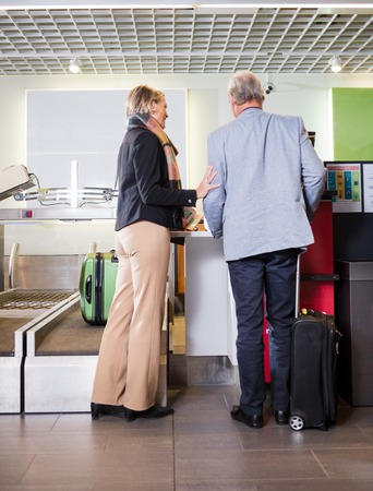 Senior Business Couple Standing At Airport Check-in Desk Standard-Bild