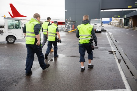 Rear View Of Male Workers Walking On Wet Runway Standard-Bild