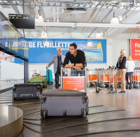 Man Waiting For Baggage From Conveyor Belt At Airport