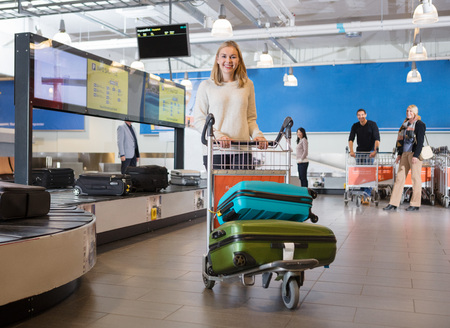 Young Woman With Luggage In Cart At Airport Foto de archivo