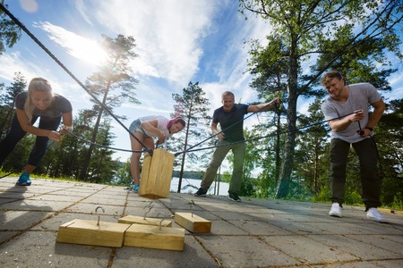Males And Females Picking Up Wooden Blocks With Ropes Standard-Bild