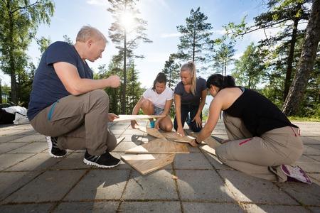 Coworkers Solving Wooden Plank Puzzle On Patio Foto de archivo
