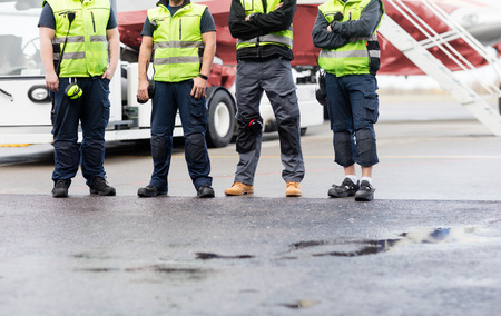Low Section Of Ground Crew Standing On Runway