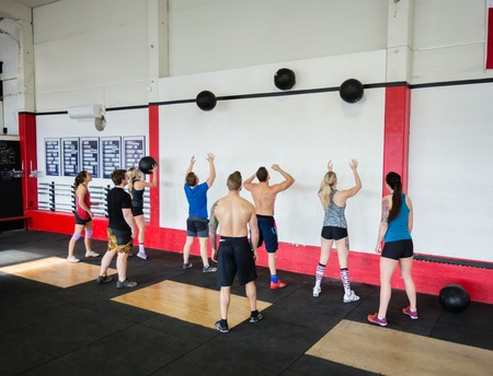 Men And Women Throwing Medicine Balls On Wall