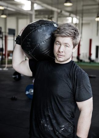 Man Carrying Medicine Ball On Shoulder In Gym Foto de archivo