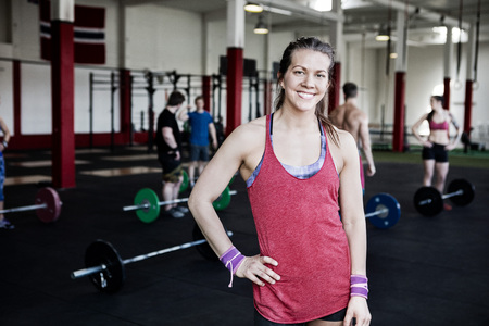 Fit Woman With Hand On Hip Standing In Fitness Center