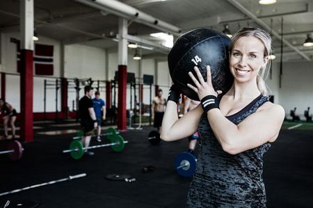 Smiling Woman Lifting Medicine Ball Foto de archivo