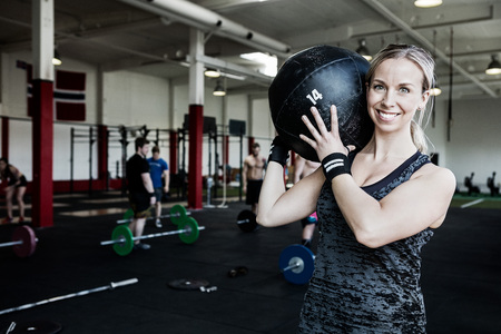 Smiling Woman Lifting Medicine Ball Standard-Bild