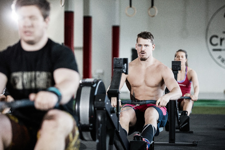 Muscular Man Exercising On Rowing Machine In Gym Standard-Bild