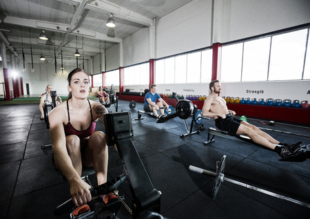 Athlete Using Rowing Machine With Friends In Fitness Center Standard-Bild