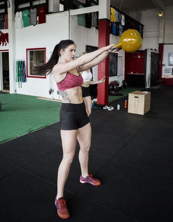 Woman Lifting Kettlebell In Gym