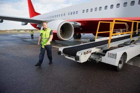 Worker Walking By Conveyor Truck With Airplane On Runway Foto de archivo