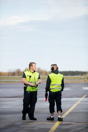 Workers In Reflective Jackets Standing On Airport Runway Foto de archivo