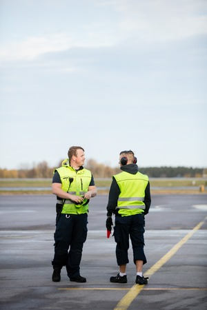 Workers In Reflective Jackets Standing On Airport Runway Standard-Bild