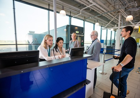 Staff Using Computer While Passengers Waiting In Airport