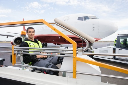 Male Worker Sitting On Luggage Conveyor Truck