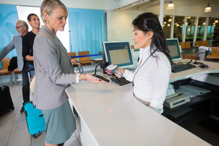 Airport Receptionist Scanning Barcode On Smart Phone Held By Bus