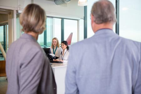 Receptionists Using Computer While Senior Business Couple Waitin Foto de archivo