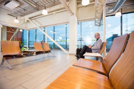 Senior Businessman Using Laptop In Airport Lobby