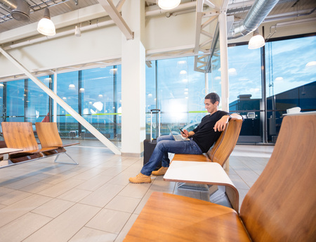 Man Using Mobile Phone While Waiting For His Flight Foto de archivo
