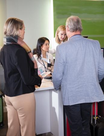 Staff Assisting Senior Passengers At Airport Check-in Desk Foto de archivo