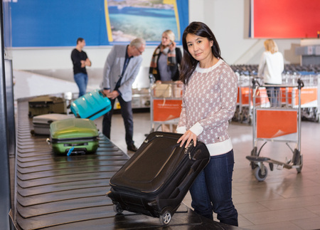 Woman Collecting Luggage At Conveyor Belt In Airport Foto de archivo