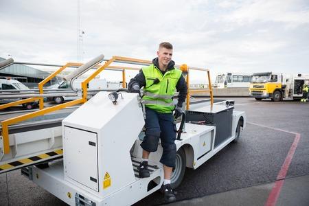 Worker Disembarking Luggage Conveyor Truck On Airport Runway