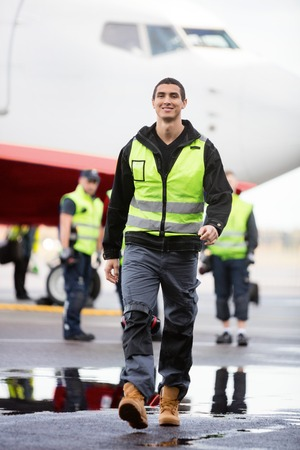 Young Male Worker Walking On Wet Runway At Airport