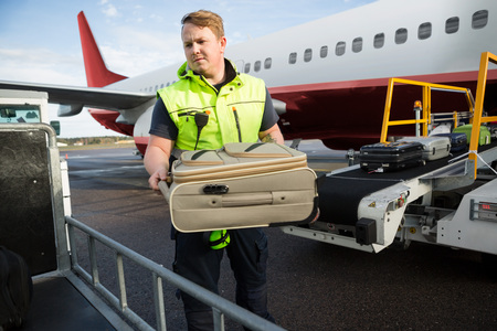 Worker Placing Luggage In Trailer Against Airplane Standard-Bild