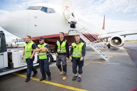Confident Ground Crew Walking Against Airplane Foto de archivo