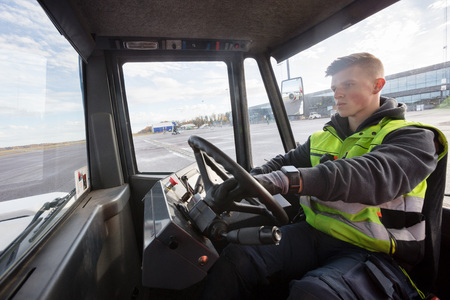 Worker Driving Towing Truck On Runway Foto de archivo
