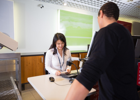 Staff Examining Passport Of Passenger At Airport Check-in